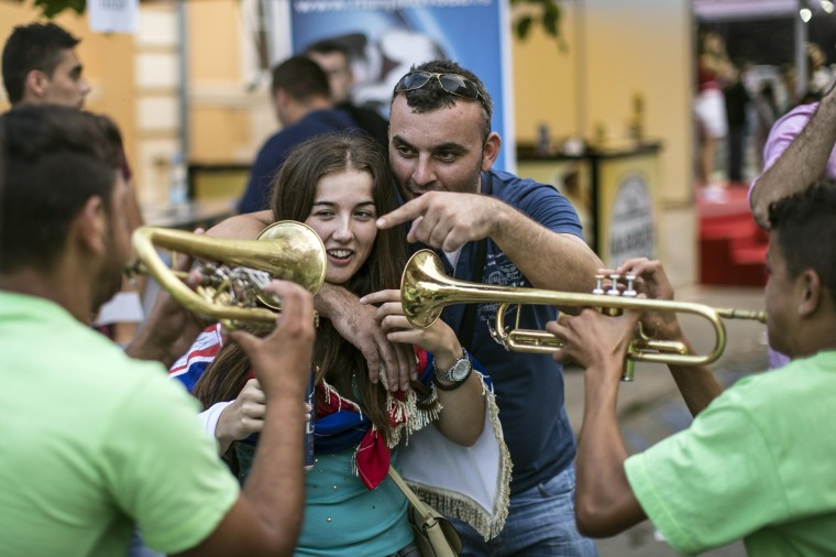 People sing and dance in a street surrounded by a band during the 54th annual brass band festival in the Serbian village of Guca. Every year Guca is swamped by thousands of people taking part in the celebration of brass band music. (Marko Djurica/Reuters)