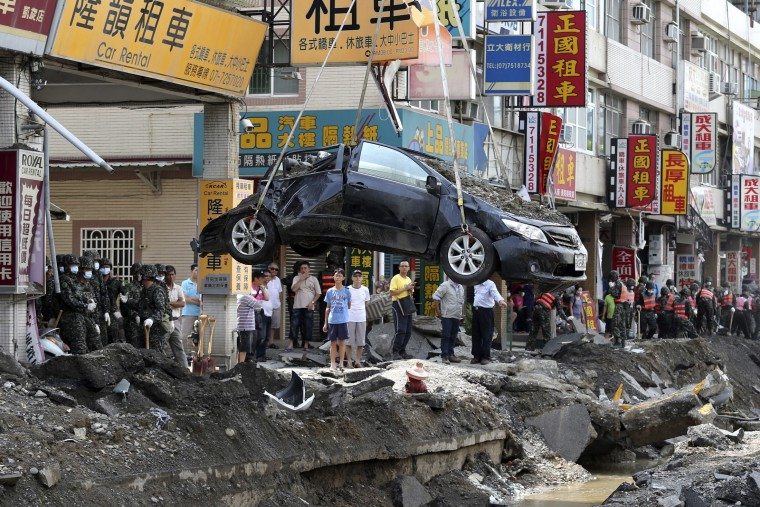 A damaged car is removed from the wreckage after an explosion in Kaohsiung, southern Taiwan. A series of explosions caused by a gas leak killed 25 people and injured 267 in Taiwan's second city on Friday, sending flames shooting 15 storeys into the air, setting ablaze entire blocks and reducing small shops to rubble. (Edward Lau/Reuters)