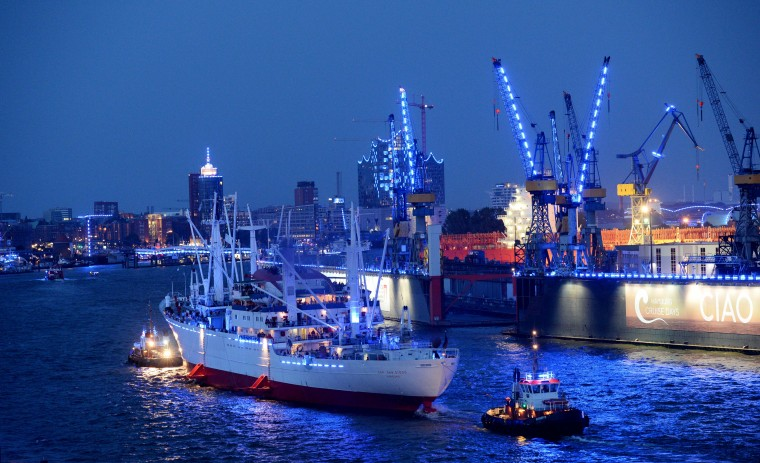 """The museum vessel """"Cap San Diego"""" passes by the illuminated harbour of Hamburg, northern Germany on the first day of the """"Hamburg Cruise Days"""". Six cruise liner are expected during the event that takes place from August 1 to 3, 2014. (Daniel Reinhardt/AFP-Getty Images)"""