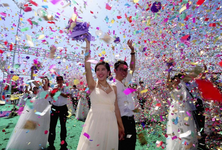 Couples celebrate during a mass wedding ceremony to mark the Qixi Festival in Shenyang, Liaoning province. According to local media, 77 couples attended the mass wedding Saturday. Qixi, also known as the Double Seventh Festival and the Chinese version of Valentine's Day, falls on the seventh day of the seventh month in the Chinese lunar calendar. (China Stringer Network/Reuters)