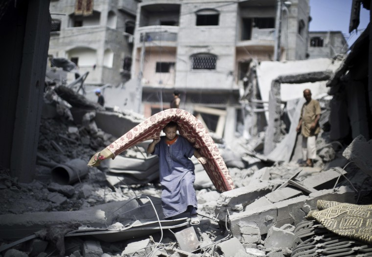 A Palestinian boy carries a mattress as he makes his way through the rubble of a house destroyed in an Israeli military strike in the Jabalia refugee camp, in the northern Gaza Strip. Israeli warplanes pounded targets in Gaza, a day after killing at least five Palestinians, and militants fired dozens of rockets into Israel after attempts to extend a three-day truce stalled. (Mahmud Hams/AFP-Getty Images)