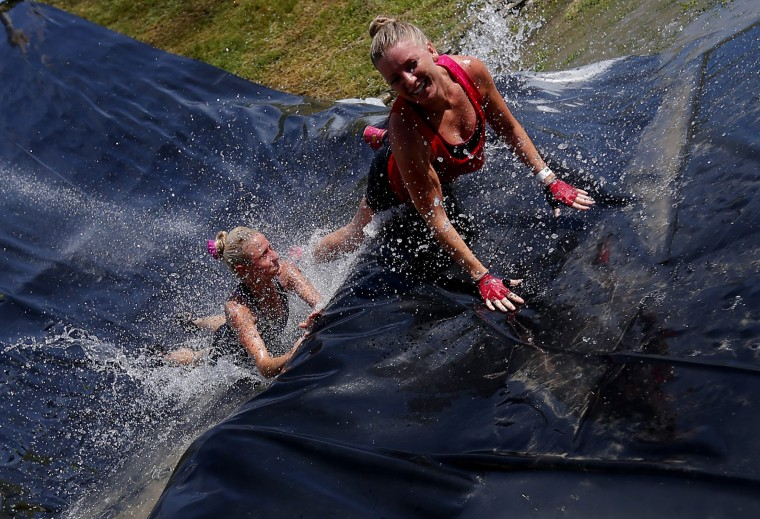 Competitors slide during the Brutal Run extreme obstacle course race in Budapest . (Laszlo Balogh/Reuters)