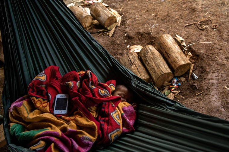 A child from the Bunong indigenous group sleeps on a hammock while a smartphone plays music in Mondulkiri, Cambodia. Cambodia's indigenous groups are at risk as their ancestral lands are being threatened by businesses interested in commercially developing the areas. On August 9, the UN focuses on the rights of the World's Indigenous People on International Indigenous People's Day. (Hannah Reyes/Getty Images)