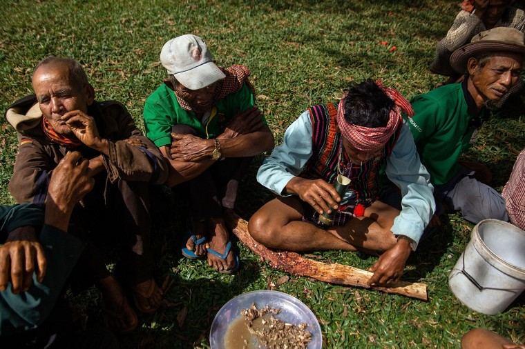 At an event to rehearse music for International Indigenous Peple's Day, men from the Bunong indigenous community share wine and tobacco in Mondulkiri, Cambodia. Cambodia's indigenous groups are at risk as their ancestral lands are being threatened by businesses interested in commercially developing the areas. On August 9, the UN focuses on the rights of the World's Indigenous People on International Indigenous People's Day. (Hannah Reyes/Getty Images)