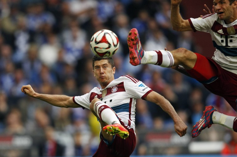Bayern Munich's Thomas Mueller and Robert Lewandowski (L) jump for a ball during their German first division Bundesliga soccer match against Schalke 04 in Gelsenkirchen. (Ina Fassbender/Reuters)