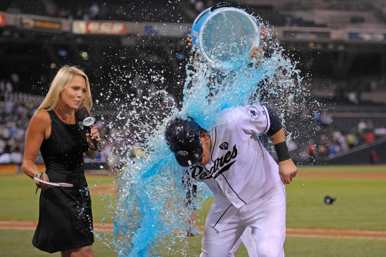 San Diego Padres catcher Yasmani Grandal (8) is doused by shortstop Everth Cabrera (2) while being interviewed after driving in the winning run during the twelfth inning against the Los Angeles Dodgers to beat the Dodgers 3-2 at Petco Park. (Jake Roth/USA Today Sports)