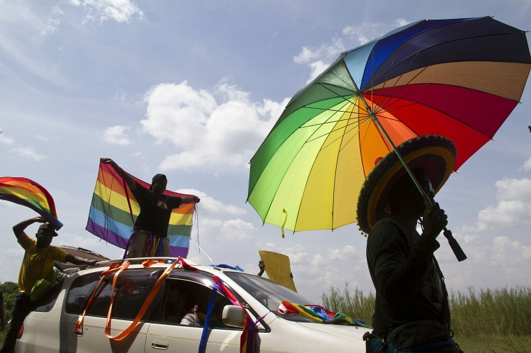 "A person holds an umbrella bearing the colors of the rainbow flag as others wave flags during the the first gay pride rally since the overturning of a tough anti-homosexuality law, which authorities have appealed, in Entebbe. The overturned law, condemned as ""abominable"" by rights groups but popular among many Ugandans, called for proven homosexuals to be jailed for life. (Isaac Kasamani/AFP-Getty Images)"