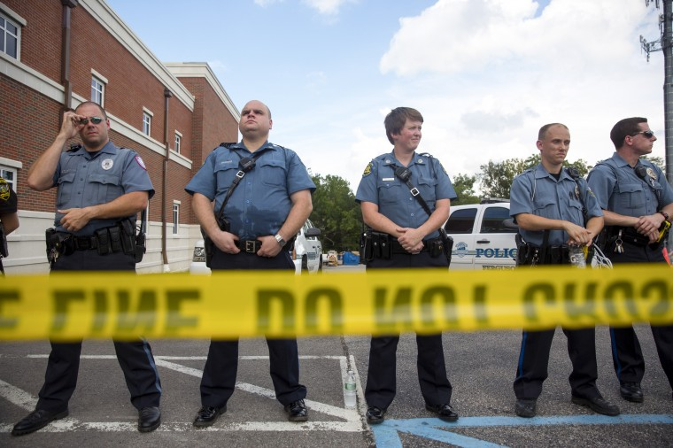 Police stand guard during a rally for Michael Brown outside the Ferguson Police Department in Ferguson, Missouri. Michael Brown, an 18-year-old unarmed teenager, was shot and killed by Ferguson Police Officer Darren Wilson on August 9. His death caused several days of violent protests along with rioting and looting in Ferguson. (Aaron P. Bernstein/Getty Images)