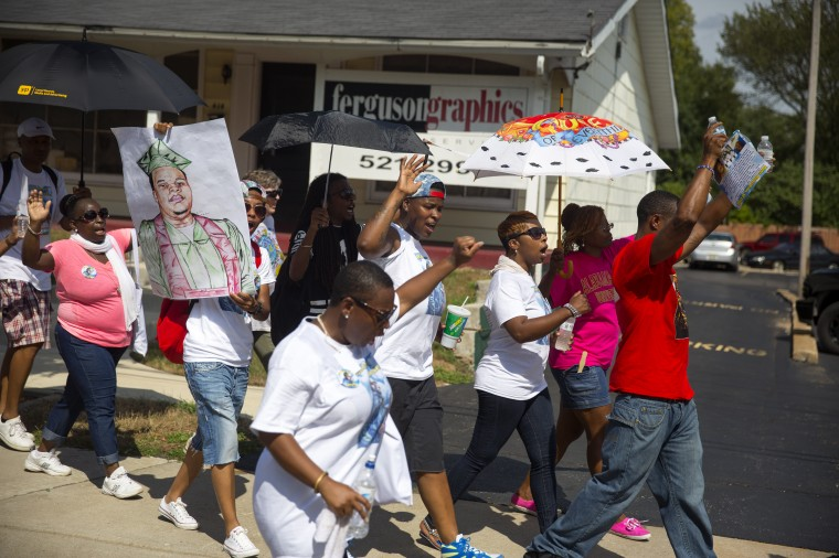 Protesters, including Lesley McFadden (with white umbrella) march to demand justice for Michael Brown in Ferguson, Missouri. Michael Brown, an 18-year-old unarmed teenager, was shot and killed by Ferguson Police Officer Darren Wilson on August 9. His death caused several days of violent protests along with rioting and looting in Ferguson. (Aaron P. Bernstein/Getty Images)