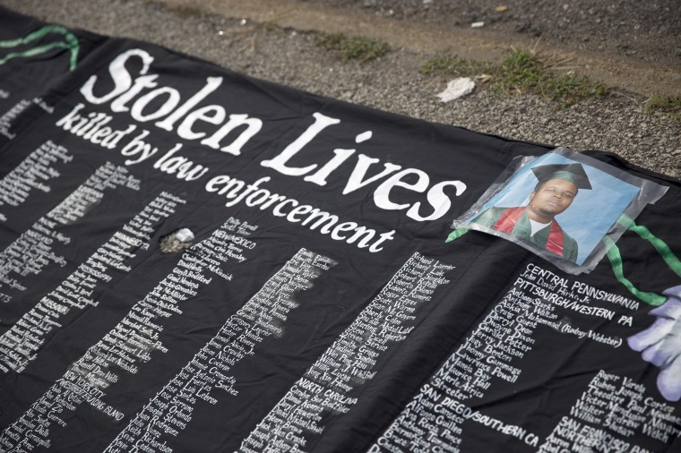 A picture of Michael Brown is seen on a banner at a rally in Ferguson, Missouri. Michael Brown, an 18-year-old unarmed teenager, was shot and killed by Ferguson Police Officer Darren Wilson on August 9. His death caused several days of violent protests along with rioting and looting in Ferguson. (Aaron P. Bernstein/Getty Images)