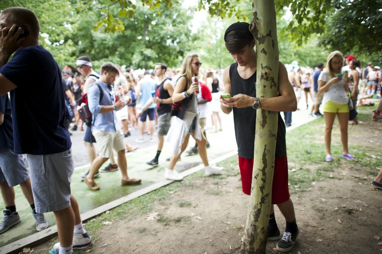 T. J. Bourne, 18, rests on a tree and texts on his mobile phone at the Made in America festival in Philadelphia. The two day music festival is organized by Jay-Z and will have a twin concert in Los Angeles. (Mark Makela/Reuters)