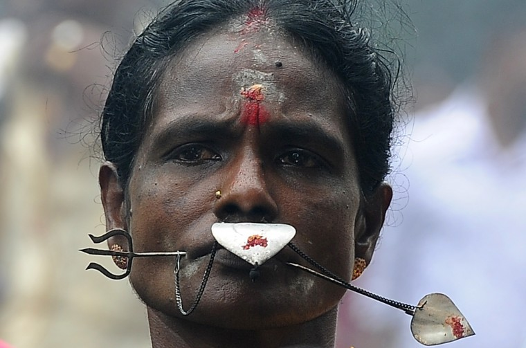 A Sri Lankan Tamil Hindu devotee, with piercings through her face, participates in the Vel Hinduism festival in Colombo. Ethnic Tamils, who are mainly followers of Hinduism, are the main minority community in the island which is emerging from nearly four decades of ethnic conflict which had claimed up to 100,000 lives (Lakruwan Wanniarachchi/AFP-Getty Images)