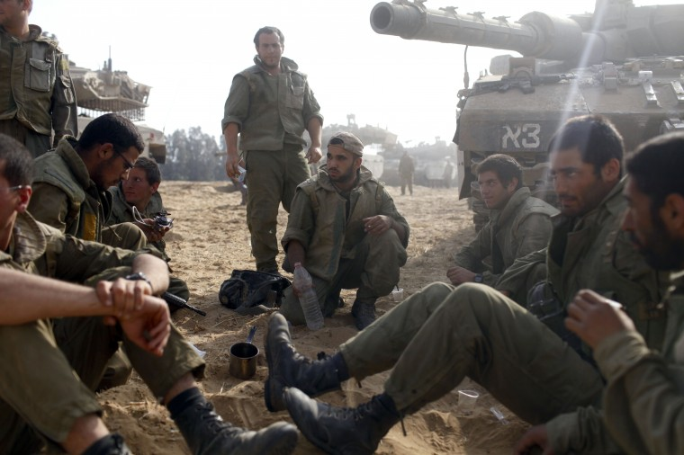Israeli soldiers sit next to a tank in a deployment area on Israel's border with the Gaza Strip. The Israeli military on Friday cited indications that the officer, Second Lt. Hadar Goldin, 23, was taken captive in Rafah, a city in the Gaza Strip's south. Two other soldiers were killed in the attack, raising the number of Israeli military fatalities to 63. The announcement came not long after a 72-hour humanitarian cease-fire agreed upon by Israel and Hamas collapsed within two hours of being launched. (Lior Mizrahi/Getty Images)