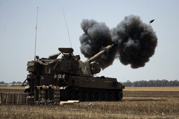 """An Israeli artillery unit fires a 155mm shell towards targets in the Gaza Strip from their position near Israel's border with the Palestinian enclave. The Israeli army informed residents of Beit Lahiya in northern Gaza that it was """"safe"""" to return to their homes, as witnesses said troops were seen withdrawing from the area. (David Buimovitch/AFP-Getty Images)"""