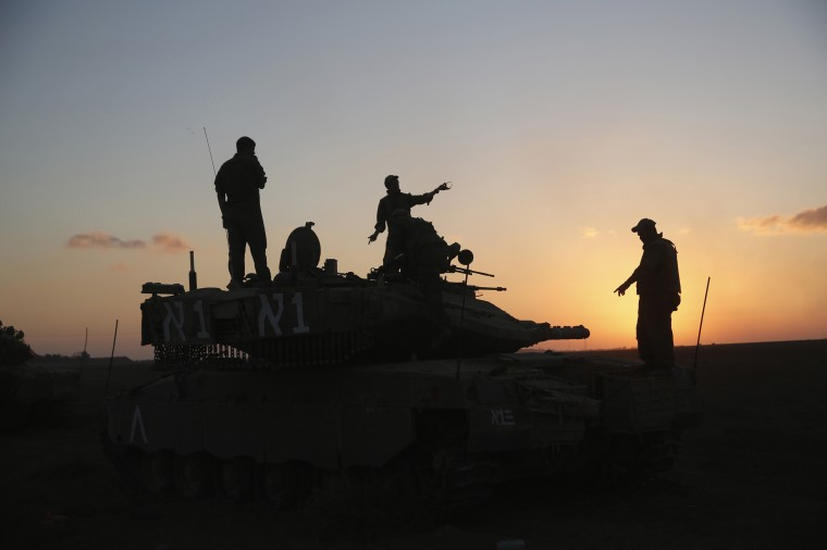 Israeli soldiers stand on top of a tank near the Israeli border with the Gaza Strip August 2, 2014. Israel is prepared to continue fighting Palestinian guerrillas in the Gaza Strip after the army completes its primary mission of destroying cross-border tunnels from the territory, Prime Minister Benjamin Netanyahu said on Saturday. (Baz Ratner/Reuters)6