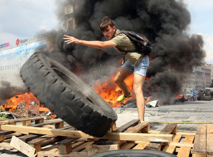 A resident of Kiev throws a tyre as he cleans up Maidan self-defence activists camp in front of burning tents in Kiev as thousands of people came to remove barricades from the city's central Independence Square, also known as Maidan, and free Khreshchatyk Street for traffic. Some few hundreds of Maidan activists still live in the tent camp set in the center of the city that upsets the vast majority of the local residents as the self-defence activist transformed the iconic place into a hotbed crime, drunkenness and instability. The Kievites assert that the present inhabitants of the current Maidan discredited the very concept of Maidan and call them Alco-Maidan.. (Volodymyr Petrov/AFP-Getty Images)