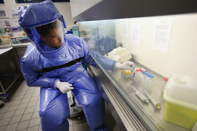 A doctor for tropical medicine prepares a blood sample for analysis during a demonstration for the media of ebola treatment capabilities at Station 59 at Charite hospital on August 11, 2014 in Berlin, Germany. The specialized quarantine unit at Station 59 is among a handful of facilities in Germany nationwide that are capable of handling ebola cases. According to media reports a German medical student currently in Ruanda is showing signs of the disease, though should he in fact have ebola it is so far unclear whether he would be flown to Germany for treatment. The disease has so far claimed over 1,000 lives in western Africa in recent weeks. (Photo by Sean Gallup/Getty Images)