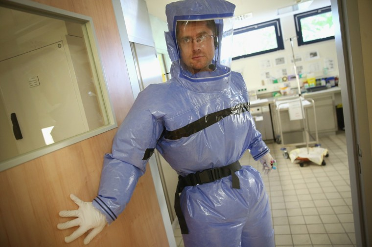 A doctor for tropical medicine wearing an isolation prepares to enter a laboratory during a demonstration for the media of ebola treatment capabilities at Station 59 at Charite hospital on August 11, 2014 in Berlin, Germany. The specialized quarantine unit at Station 59 is among a handful of facilities in Germany nationwide that are capable of handling ebola cases. According to media reports a German medical student currently in Ruanda is showing signs of the disease, though should he in fact have ebola it is so far unclear whether he would be flown to Germany for treatment. The disease has so far claimed over 1,000 lives in western Africa in recent weeks. (Photo by Sean Gallup/Getty Images)