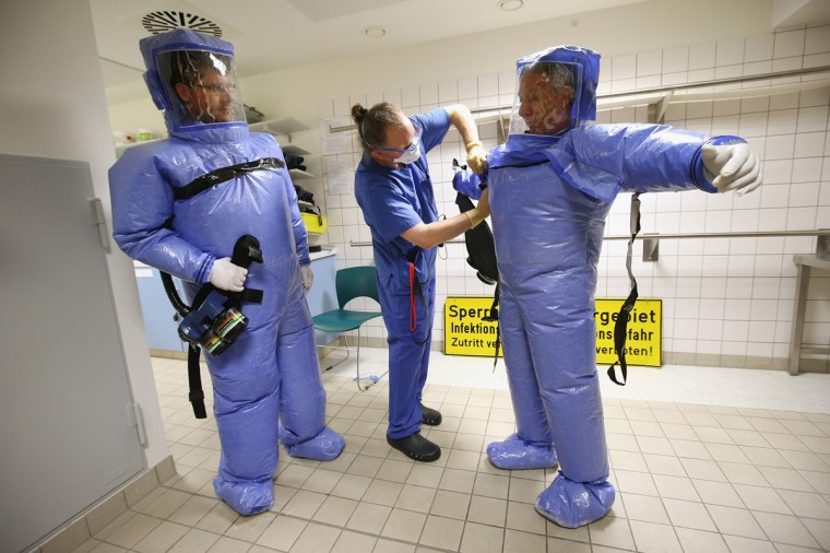 A nurse helps a doctor for tropical medicine and a nurse take off their isolation suits following a demonstration for the media of ebola treatment capabilities at Station 59 at Charite hospital on August 11, 2014 in Berlin, Germany. The specialized quarantine unit at Station 59 is among a handful of facilities in Germany nationwide that are capable of handling ebola cases. According to media reports a German medical student currently in Ruanda is showing signs of the disease, though should he in fact have ebola it is so far unclear whether he would be flown to Germany for treatment. The disease has so far claimed over 1,000 lives in western Africa in recent weeks. (Photo by Sean Gallup/Getty Images)