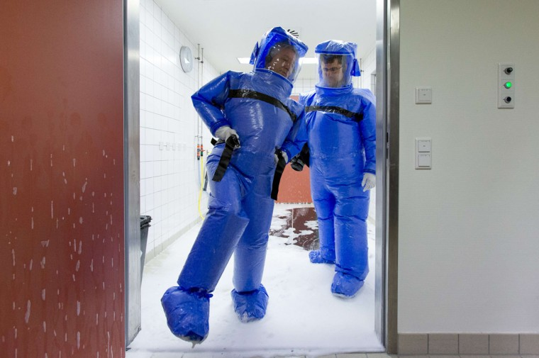 Doctor for tropical medicine Florian Steiner (R) and ward physician Thomas Klotzkowski step out of a disinfection chamber after cleaning their protective suits, at the quarantine station for patients with infectious diseases at the Charite hospital in Berlin August 11, 2014. The isolation ward at the Charite is one of several centres in Germany equipped to treat patients suffering from ebola and other highly infectious diseases, the clinic's doctor for tropical medicine Florian Steiner said. Ebola is one of the deadliest diseases known to humanity. It has no proven cure and there is no vaccine to prevent infection. The most effective treatment involves alleviating symptoms that include fever, vomiting and diarrhoea. The rigorous use of quarantine is needed to prevent its spread, as well as high standards of hygiene for anyone who might come into contact with the disease. (Thomas Peter/Reuters)