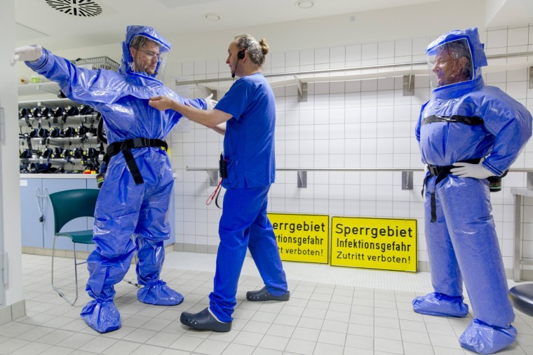 Ward physician Thomas Klotzkowski and doctor for tropical medicine Florian Steiner (L) put on protective suits at the quarantine station for patients with infectious diseases at the Charite hospital in Berlin August 11, 2014. (Thomas Peter/Reuters)