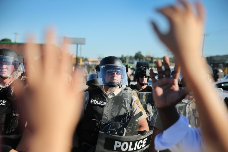 A child, who was being held by her mother who was protesting the shooting death of teenager Michael Brown, holds up her hands after police ordered them off the street by on August 13, 2014 in Ferguson, Missouri. Brown was shot and killed by a Ferguson police officer on Saturday. Ferguson, a St. Louis suburb, has experienced three days of violent protests since the killing. (Photo by Scott Olson/Getty Images)