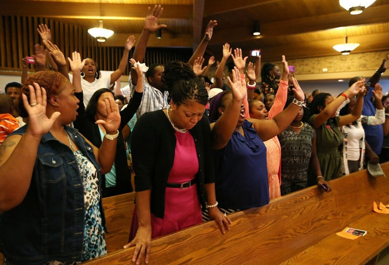 "Attendees chant ""Hands up, don't shoot"" during a gathering with Michael Brown's family and Rev. Al Sharpton at the Greater St. Mark Missionary Baptist Church on Tuesday, Aug. 12, 2014, in Dellwood, Mo. The gathering at the church was in response to the police shooting of 18-year-old Michael Brown on Saturday. (Chris Lee/St. Louis Post-Dispatch/MCT)"
