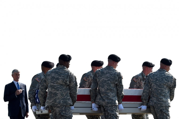 U.S. Army soldiers carry the flag-draped transfer case containing the remains of U.S. Army Maj. Gen. Harold J. Greene during a dignified transfer, as U.S. Army Secretary John McHugh holds his hand over his heart, at Dover Air Force Base on August 7, 2014 in Dover, Delaware. According to reports, Greene, who was from Schenectady, New York, assigned to the Combined Security Transition Command, was killed after his unit was attacked in Afghanistan. (Photo by Patrick Smith/Getty Images)