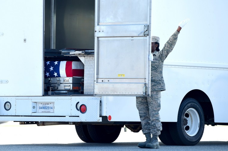 U.S. Air Force Door Attendant Senior Airman Kristina C. Barr, shuts the door of the transfer vehicle, as the flag-draped transfer case containing the remains of U.S. Army Maj. Gen. Harold J. Greene rest inside during a dignified transfer at Dover Air Force Base on August 7, 2014 in Dover, Delaware. According to reports, Greene, who was from Schenectady, New York, assigned to the Combined Security Transition Command, was killed after his unit was attacked in Afghanistan. (Photo by Patrick Smith/Getty Images)