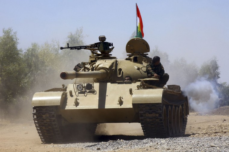 Kurdish peshmerga troops patrol in a tank during an operation against Islamic State militants in Makhmur, on the outskirts of the province of Nineveh August 7, 2014. The United States began to drop relief supplies to beleaguered Yazidi refugees fleeing Islamist militants in Iraq, but there was no immediate sign on Friday of U.S. air strikes to halt the sweeping advance of Islamic State fighters. Picture taken August 7, 2014. (REUTERS/Stringer)