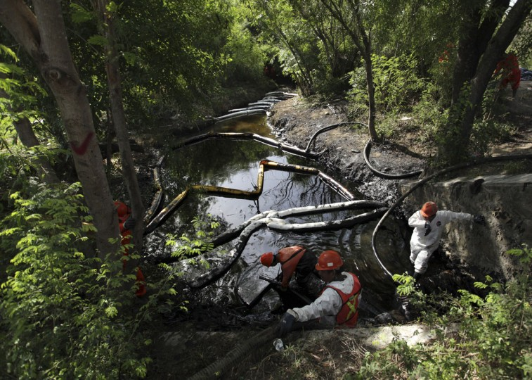 Workers try to clean up leaking oil at a stream in Cadereyta August 21, 2014. (REUTERS/Daniel Becerril)
