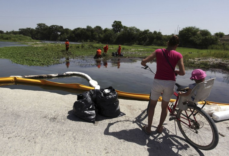 A woman observes as workers try to clean leaking oil in the river San Juan in Cadereyta August 21, 2014. (REUTERS/Daniel Becerril)