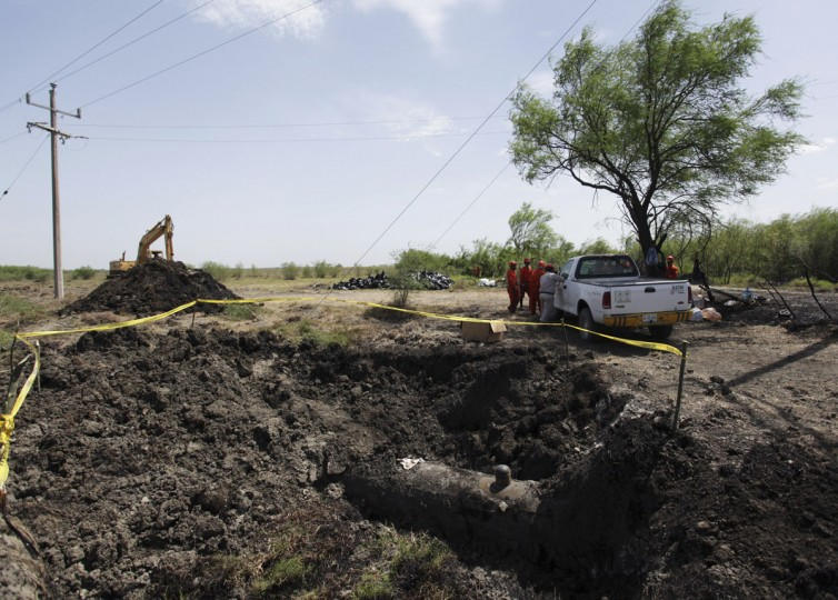 A part of the oil pipeline where thieves had tried to tap into, is seen uncovered and surrounded by yellow tape in Cadereyta August 21, 2014. (REUTERS/Daniel Becerril)