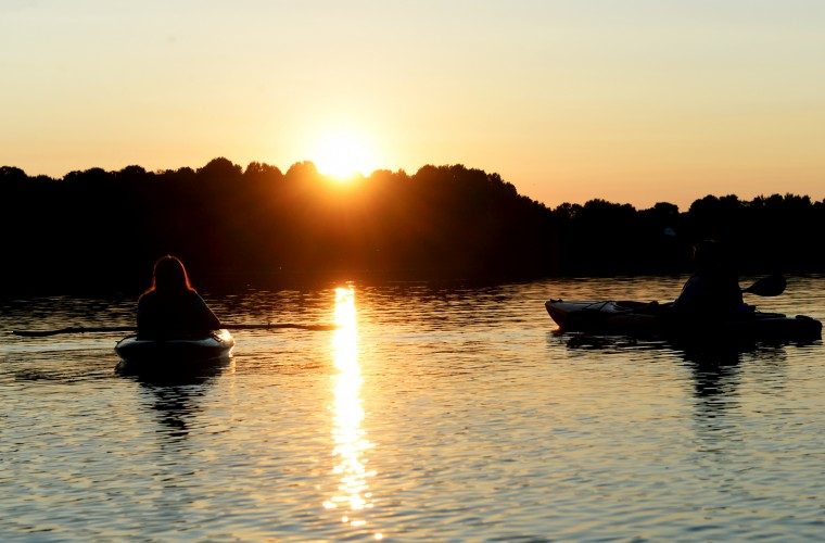 Members of a sunset kayak tour of Piney Run Reservoir in Sykesville watch the sun go down over the trees, Saturday, Aug. 16, 2014. (Jon Sham/BSMG)