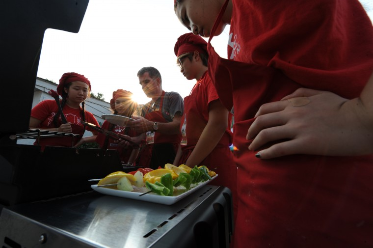 From left, team Alba's Army members Joanna Park, 13, of Clarksville, Marianna Ghirardelli, 15, of Columbia, her dad Tom Ghirardelli, of Columbia, James Shon, 14, of Columbia and Katelyn Park, 15, of Clarksville, begin to grill during the Iron Chef competition at the Howard County Fair in West Friendship, Thursday, Aug. 7, 2014. (Jon Sham/BSMG)