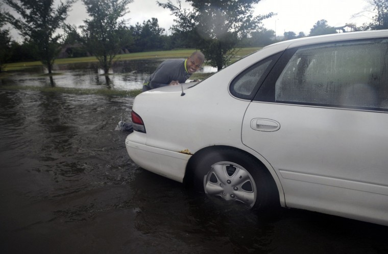 Clifton McCrary of Baltimore pushes a car through a flooded South Hanover St. before Reedbird Ave. in Baltimore on Tuesday afternoon. McCrary pushed around a dozen cars through the water and helped direct traffic until the water level lowered. (Al Drago/Baltimore Sun)