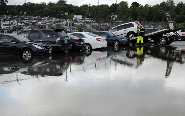 A tow truck driver moves vehicles to a dry section of the lot as flood water recedes Tuesday from a section of BWI's long term parking Lot A. (Kim Hairston/The Baltimore Sun)