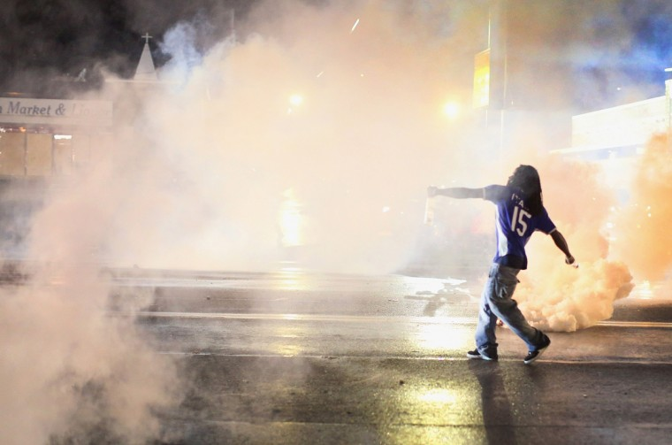 A demonstrator throws a grenade back at police after a brief clash on August 15, 2014 in Ferguson, Missouri. Police sprayed pepper spray, shot smoke, gas and flash grenades at protestors before retreating. Several businesses were looted following the skirmish as police held there position nearby. Violent outbreaks have taken place in Ferguson since the shooting death of Michael Brown by a Ferguson police officer on August 9. (Photo by Scott Olson/Getty Images)