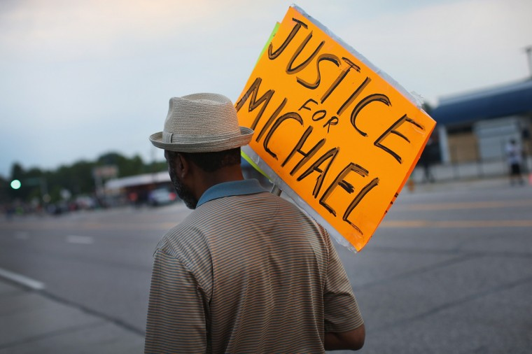 A demonstrator protests along Florissant Avenue on August 16, 2014 in Ferguson, Missouri. Violent protests have erupted nearly every night along the street since the shooting death of teenager Michael Brown by a Ferguson police officer on August 9. (Photo by Scott Olson/Getty Images)