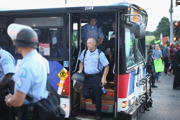 Police arrive by bus before being deployed to keep peace along Florissant Avenue on August 16, 2014 in Ferguson, Missouri. Violent protests have erupted nearly every night along the street since the shooting death of teenager Michael Brown by a Ferguson police officer on August 9. (Photo by Scott Olson/Getty Images)