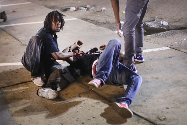 A man gets help after being overcome by tear gas that police launched at demonstrators protesting the killing of teenager Michael Brown on August 17, 2014 in Ferguson, Missouri. Police shot smoke and tear gas into the crowd of several hundred as they advanced near the police command center which has been set up in a shopping mall parking lot. Brown was shot and killed by a Ferguson police officer on August 9. Despite the Brown family's continued call for peaceful demonstrations, violent protests have erupted nearly every night in Ferguson since his death. (Photo by Scott Olson/Getty Images)