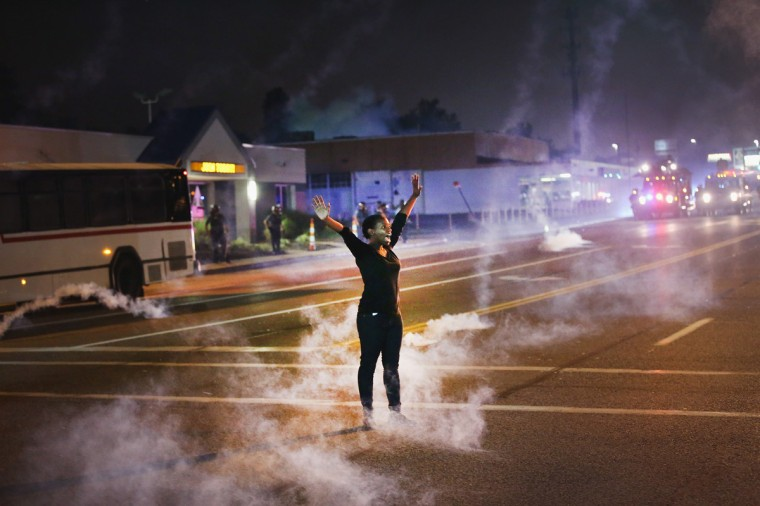 Tear gas reigns down on a woman standing with her arms raised in the street after a demonstration over the killing of teenager Michael Brown by a Ferguson police on August 17, 2014 in Ferguson, Missouri. Despite the Brown family's continued call for peaceful demonstrations, violent protests have erupted nearly every night in Ferguson since his August 9, death. (Photo by Scott Olson/Getty Images)