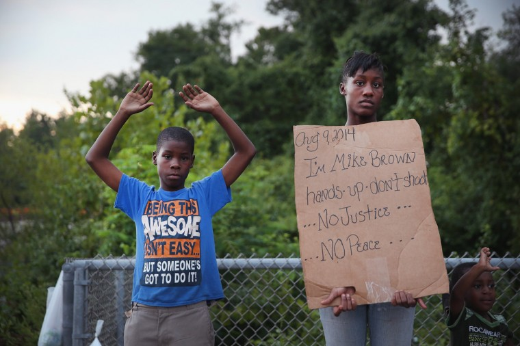 Leo Walker (L) and his sister Letrece protest the killing of teenager Michael Brown on August 17, 2014 in Ferguson, Missouri. Despite the Brown family's continued call for peaceful demonstrations, violent protests have erupted nearly every night in Ferguson since his death. (Photo by Scott Olson/Getty Images)
