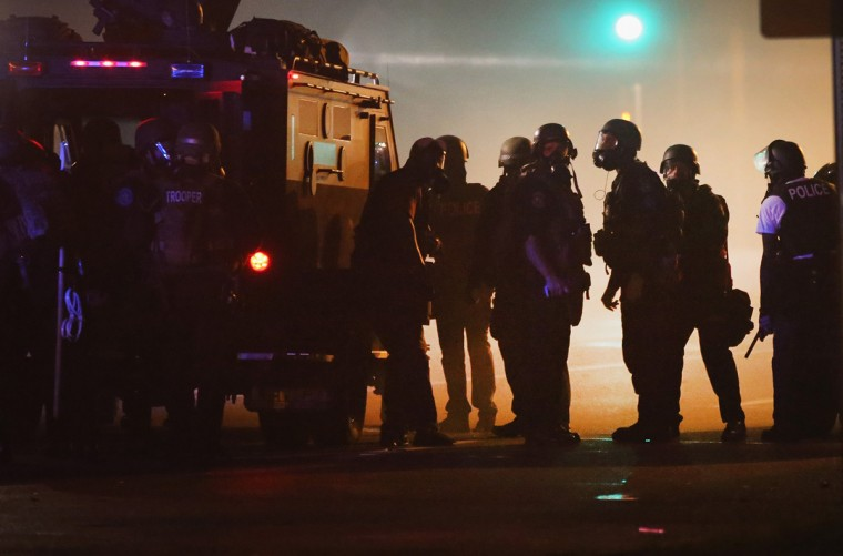Police attempt to control demonstrators protesting the killing of teenager Michael Brown on August 18, 2014 in Ferguson, Missouri. Police shot smoke and tear gas to disperse the protestors with as they became unruly. Brown was shot and killed by a Ferguson police officer on August 9. Despite the Brown family's continued call for peaceful demonstrations, violent protests have erupted nearly every night in Ferguson since his death. (Photo by Scott Olson/Getty Images)