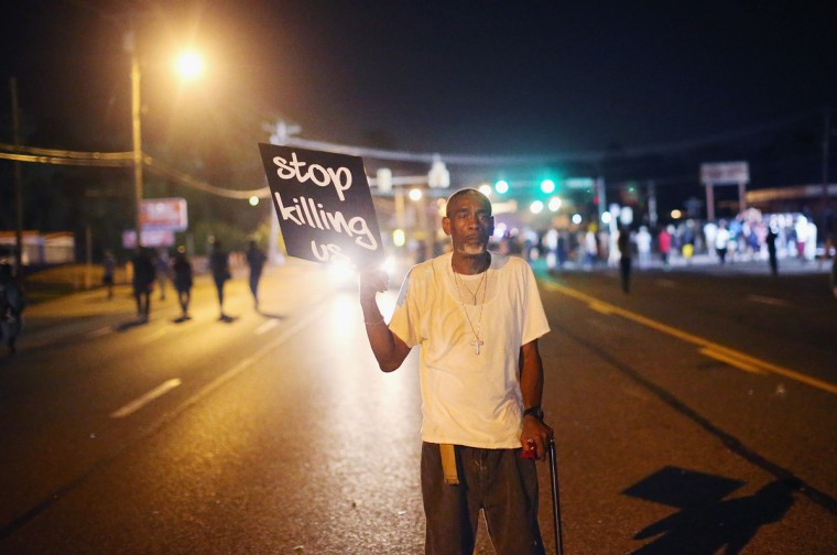 Frederick Scott protests the killing of teenager Michael Brown on August 18, 2014 in Ferguson, Missouri. Brown was shot and killed by a Ferguson police officer on August 9. Despite the Brown family's continued call for peaceful demonstrations, violent protests have erupted nearly every night in Ferguson since his death. (Photo by Scott Olson/Getty Images)