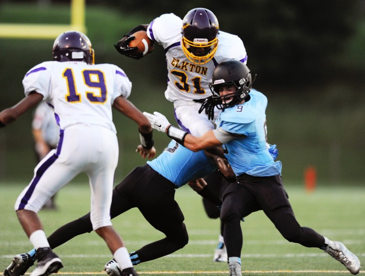 Elkton's Zy'phere Ruffin, No. 31, tries to jump over C. Milton Wright defenders Brad Martin, right, and Josh Bailey, second from left, during a football game at C. Milton Wright High in Bel Air, Friday, Sept. 5, 2014. Elkton teammate Tyrus Woodard, left, was helping to block before the collision. (Jon Sham/BSMG)