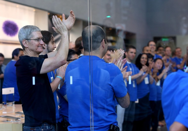 Apple CEO Tim Cook (L) cheers with Apple Store employees before opening the store to sell the new iPhone 6 on September 19, 2014 in Palo Alto, California. Justin Sullivan/Getty Images