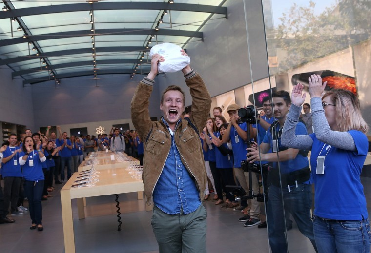 Patrick Tuntland holds up his new iPhone 6 Plus as he leaves an Apple Store on September 19, 2014 in Palo Alto, California. Hundreds of people lined up to to purchase the new iPhone 6 and iPhone 6 Plus that went on sale today. Justin Sullivan/Getty Images