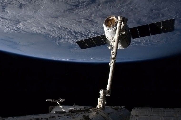 """This March 3, 2013 NASA image from video shows the SpaceX capsule Dragon attached to the Canada Arm at the International Space Staion (ISS). A SpaceX rocket exploded in midair during a test flight August 22, 2014 in McGregor, Texas, though no one was injured, as the company seeks to develop a spacecraft that can return to Earth and be used again. """"During the flight, an anomaly was detected in the vehicle and the flight termination system automatically terminated the mission,"""" the company said in a statement. SpaceX is competing with other companies -- including Boeing, Sierra Nevada and Blue Origin -- to be the first commercial outfit to take astronauts to space, possibly as early as 2017. Until then, the world's astronauts must rely on Russian Soyuz spacecraft at a cost of $70 million per seat. (Chris Hadfield/AFP/Getty Images)"""