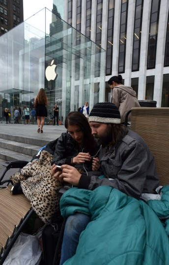 "Moon Ray (L) and her husband Jason Ray talk on skype as they wait in line September 9, 2014 outside the Apple Store on 5th Avenue in New York. Tech trend-setter Apple charts its future course Tuesday amid expectations for new big-screen iPhones and possibly an ""iWatch"" which could shake up the world of wearable computing. Apple has maintained its customary arch silence, but a frenzy of speculation suggests a push into a new segment as it seeks to broaden the appeal of its iconic iPhone. Don Emmert/AFP/Getty Images"